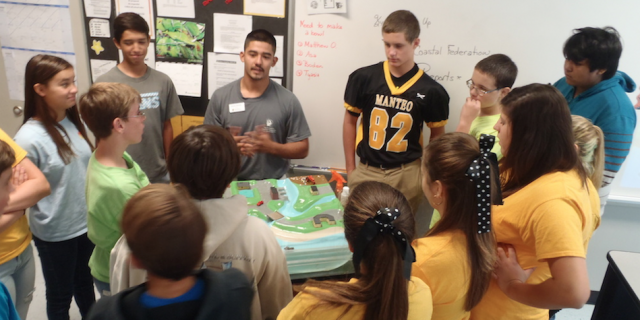 Education intern Daniel Salazar, leads a student session at Manteo Middle School using the stormwater model demonstration.