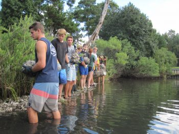Students line up and pass along oyster bags at an oyster reef construction.
