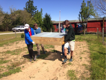 Boy Scouts help install raised beds they built as demonstration gardens