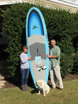 Paddleboard winners Kevin Durocher and Pam Van Velsor pose with their dog, Largo, with the paddleboard they won from the Surfside Shrimp Boil.