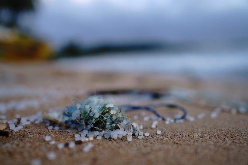 Bead-like microplastics on the sand of a beach.